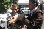 An ICRC staff member helps retired Major Gunja Karki adjust his artificial arm.