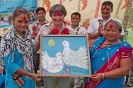 Rajhena, Banke district, Nepal. ICRC head of delegation Sylvie Thoral receives a souvenir painting from accompaniers and members of a support group during a ceremony to inaugurate a Chautari (resting place) that the families of missing persons built in memory of their relatives.