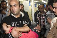 Gaza City. A man carries a wounded girl into a hospital after an air strike, 14 November 2012.
