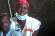 Touba, Senegal. A Senegalese Red Cross volunteer with one of the 300 children helped during the Magal.