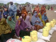 Southern Somalia. Middle Juba region, Jilib district. Female beneficiaries of a food distribution at a camp for the displaced. Each woman, head of family, resident or internally displaced person sits on a pile consisting of enough food rations to last a month.