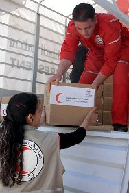 Dar'a, Syria. Red Crescent staff distribute food and other relief goods.