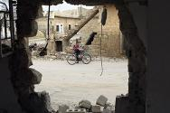 Atareb, Idlib governorate, Syria. A boy rides his bike through a recently-shelled area.