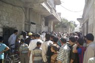 Houla, Syria. People gather outside a bakery to buy bread.