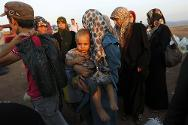Idlib province, Syria. Civilians fleeing the fighting in Aleppo wait to cross into Turkey at an unofficial border crossing.
