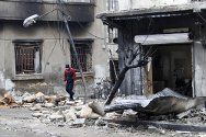 Homs, Syria. A man walks past damaged buildings.
