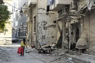 A girl carries a bag past damaged shops.