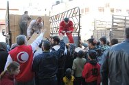 Idlib, Syria. Staff distribute food parcels in front of the SARC warehouse.