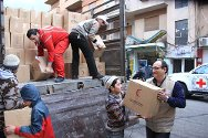 Homs. Local people help SARC volunteers unload food parcels for distribution to people who have fled their homes.