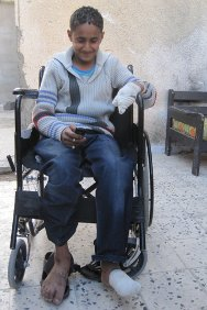 Sirte, Libya. Hosam plays with his mobile phone. He lost three fingers and two toes playing with an unexploded device.