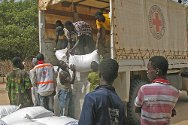 Koussabel, Casamance, Senegal. Senegalese Red Cross volunteers and young men from the village unload sacks of rice.