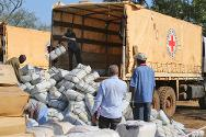 Staff unload an ICRC truck containing clothing, tarpaulins, blankets and sleeping mats for Sudanese refugees who have fled to South Sudan.