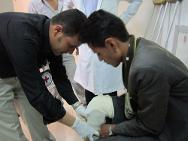 ICRC ortho technician is helping Noureddine to wear his new artificial limb. Now he can walk again on his feet and get rid of his crutch.