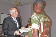 "Zimbabwe. At the end of the ""train-the-trainer"" course for humanitarian mine action instructors, the head of the ICRC's Zimbabwe delegation presents each officer with a certificate."