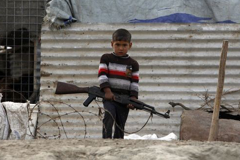 Trials ahead for a global ATT: A boy holds an Ak47 in Nassiriya, Iraq.