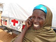 A young Somali woman in Dadaab refugee camp in Kenya is calling her relatives through the ICRC/Kenya Red Cross family links mobile phone service.