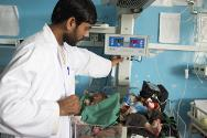 Mirwais Hospital, Kandahar, Afghanistan. A premature infant under special medical care in the nursery room of the paediatric ward. A medic observes a baby in an incubator.
