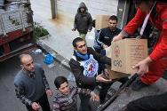 Syria, Homs. Local people help Syrian Arab Red Crescent volunteers unload food parcels from a truck into a warehouse.