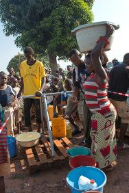 A woman who has taken refuge with thousands of others at the Bangui airport fetches water at a fountain provided by the ICRC.