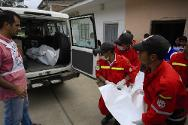 Jambaló, Cauca, Colombia, 12 July 2012. ICRC staff, helped by local firefighters, transfer the remains of two air crew members.