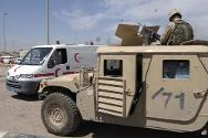 Baghdad. Iraqi Red Crescent ambulance and a military tank cross paths in the town.