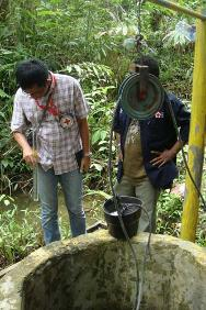 An ICRC water and habitat engineer examines the quality of water from a well in Papua.