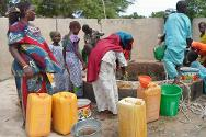 Women fill containers with clean water at one of the wells the ICRC has renovated. The influx of people fleeing Nigeria has created a water shortage, with some people having to drink standing water despite the major health risk.