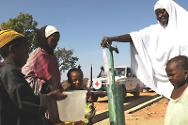 Villagers collect water from a pump renovated by the ICRC.