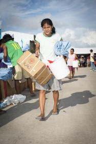 Guiuan: A young woman leaves a relief distribution site after receiving a box containing household essentials. Several evacuation centres sheltering people displaced by the typhoon are situated in Guiuan.