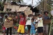 Children hold signs asking for help and food along the highway, after Typhoon Haiyan hit Tabogon town in Cebu Province, central Philippines.