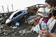 People covering their faces pass a car among the debris after Typhoon Haiyan battered Tacloban City, in central Philippines.