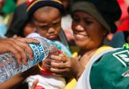 A woman receives water at a military checkpoint where she and her child wait to be airlifted to Manila in the aftermath of super typhoon Haiyan at the Tacloban airport