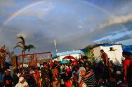 A rainbow appears above typhoon survivors desperate to catch a flight from the Tacloban airport