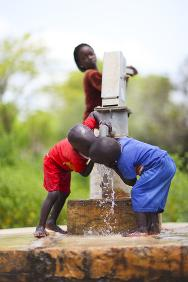 Children drink at a pump installed by the ICRC.