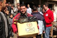 ICRC and Syrian Arab Red Crescent staff distribute food parcels in Hama, Syria.