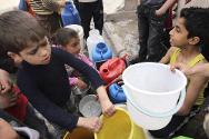 Aleppo, Syria. Children wait to collect water.