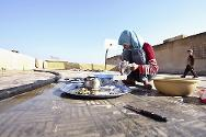 A girl does the washing up in the school where she has taken refuge.