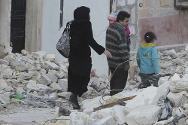 A family walks through rubble in Aleppo, Syria.