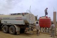Delivering water by truck in Al-Furqlus.