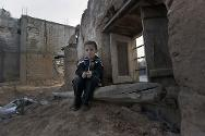 Aleppo. A child sits among the ruins of a house.