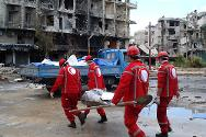A team of volunteers from the Syrian Arab Red Crescent transports a body in Helloq, Aleppo, Syria.