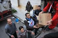 Syrian Arab Red Crescent volunteers and members of the local community unload aid supplies.