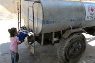 Talibseh. Homs. A displaced little girl stocks up on water from an ICRC water truck.