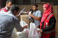 Libyan Red Crescent volunteers distribute food during Ramadan. Recipients include Syrian refugees.