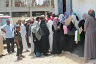 People wait to receive food. The ICRC is working with the Libyan Red Crescent to distribute food to thousands of needy families in Libya during the fasting month of Ramadan.