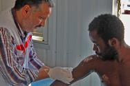 A Libyan Red Crescent medical team examines and treats migrants.
