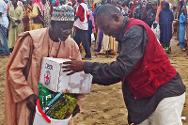 An elderly person receives emergency supplies from the Red Cross.