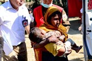 Myanmar, Thee Chaung Camp. An emergency evacuation team transfers a young child from a health post in the camp to Sittwe hospital.