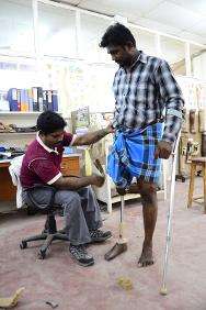 Strength for today, hope for tomorrow: an amputee tests his prosthesis with the help of a JJCDR employee.