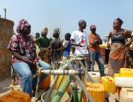 Bangui airport. The distribution of water is organized by women in the community. Families queue up with their yellow containers under a blazing sun.